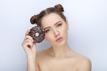 Portrait of a young woman with funny hairstyle and bare shoulders act the ape against white studio background with chocolate donut