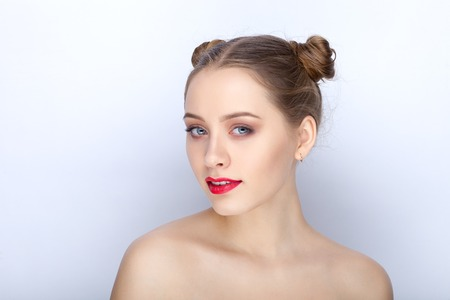 collarbone: Portrait of a young pretty woman with trendy makeup bright red lips funny bun hairstyle and bare shoulders act the ape against white studio background