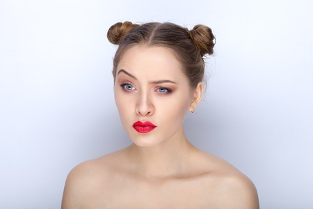 Portrait of a young pretty woman with trendy makeup bright red lips funny bun hairstyle and bare shoulders act the ape against white studio background