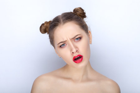 suspiciousness: Portrait of a young pretty woman with trendy makeup bright red lips funny bun hairstyle and bare shoulders act the ape against white studio background