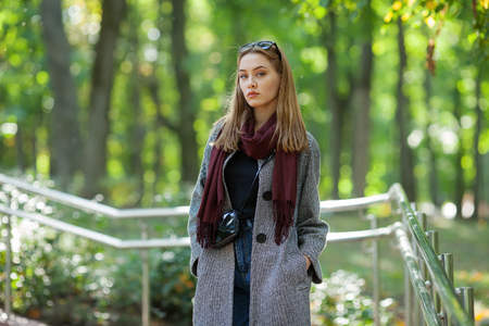 Beautiful stylish young woman in a warm scarf blue jeans trendy cozy coat walking along in fall city park Stock Photo