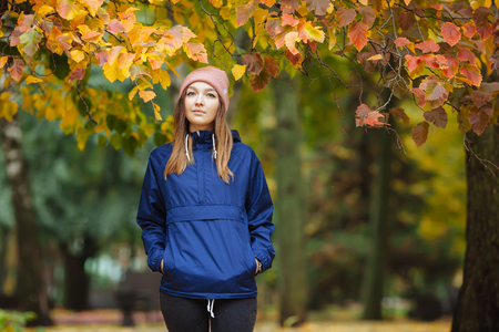 outwear: Stylish sporty brunette woman close up in trendy urban outwear posing at bridge forest city park on with golden yellow foliage. Vintage filter film saturated color. Cozy bright fall season. Stock Photo
