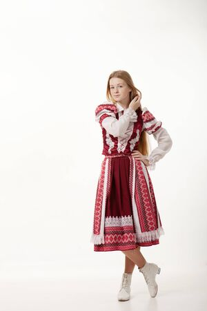 vestidos de epoca: Young beautiful redhead folk dancer woman with gorgeous long hair in traditional authentic folk costume posing isolated on white background