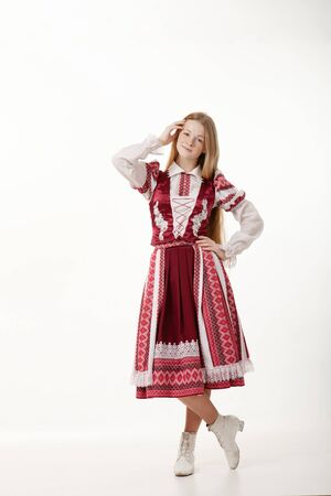 Young beautiful redhead folk dancer woman with gorgeous long hair in traditional authentic folk costume posing isolated on white background