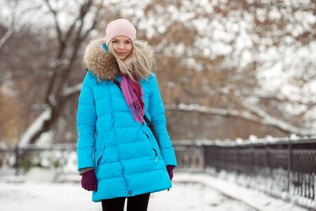 Young adorable blond woman wearing blue hooded coat strolling in snowy winter city park. Nature cold season freshness concept. Stock Photo
