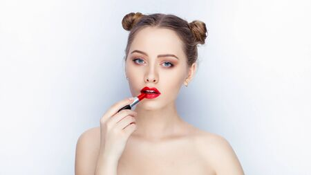 Young pretty woman trendy makeup bright red lips bun hairstyle bare shoulders act the ape with lipstick white studio background