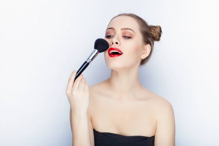 elegance fashion girls look sensuality young: Young pretty woman trendy makeup bright red lips bun hairstyle bare shoulders act the ape with brush white studio background Stock Photo