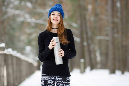 Young very positive woman in sweater blue funny knitted hat posing with thermos in winter forest park. Winter active leisure freshness concept.