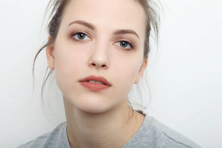 suspenso: Indoor close up portrait of charming young lady of European appearance wearing grey sweatshirt, posing isolated against white studio wall background. Emotions and facial expression concept Foto de archivo