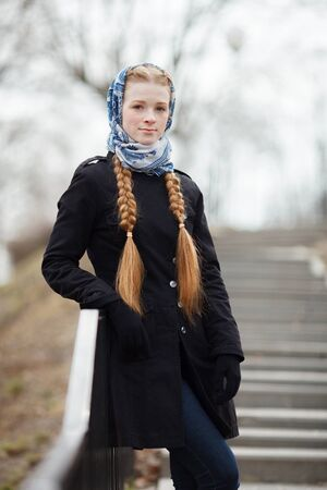 Young beautiful fashionable redhead woman with braids hairdo in blue white headcraft stylish denim black trench jacket posing on stairway in city park spring time