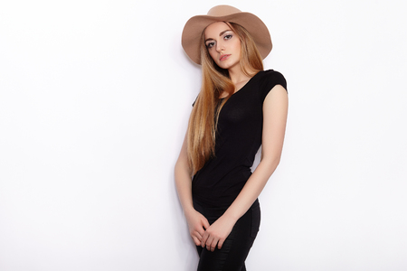 Young beautiful fashion model in women black t-shirt trendy hat black torn jeans posing in studio against white background Stock Photo