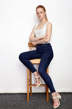 Full length portrait of young beautiful redhead beginner model woman in white t-shirt blue jeans practicing posing showing emotions sitting on bar stool white wall background