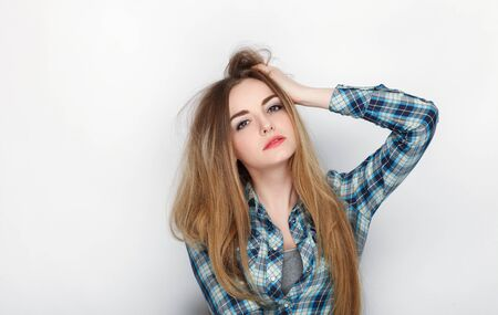 Beauty portrait of young adorable fresh looking blonde woman with hair chaos in blue plaid shirt. Emotion and facial expression concept.