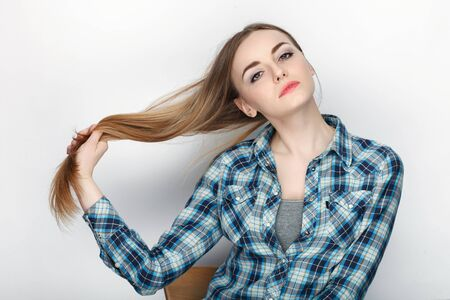 Beauty portrait of young adorable fresh looking blonde woman holding hair in blue plaid shirt. Emotion and facial expression concept.