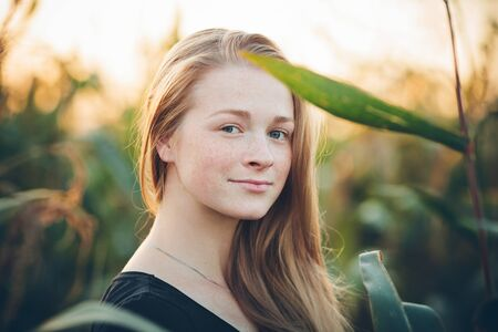Outdoors lifestyle portrait of young adorable fresh looking redhead woman with freckles gorgeous extra long hair corn field sunny evening. Emotion and facial expression concept. Stock Photo
