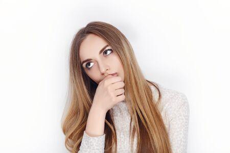 Beautiful emotional blonde female model looking pensive wear pajamas. Communication patterns concept.