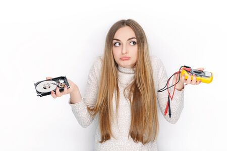Beautiful emotional blonde female model looking confused holding broken hard disk drive and multimeter.