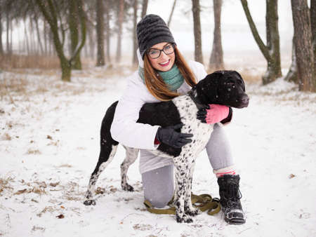 Young woman playing snow winter outdoors hugging cute adopted blind setter dog. Kindness and humanity concept. Stock Photo