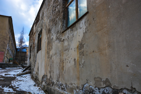 Abandoned building with cracked wall near mountains. Stock Photo
