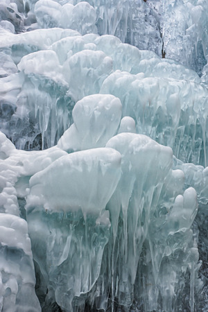 Close up view of a frozen waterfall in the river. Fresh ice in mountains. Background or texture for your project. Imagens