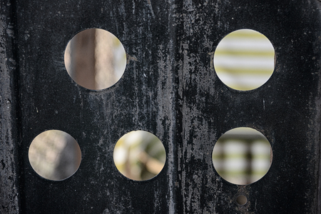 Close up metal wall with porthole-shaped windows. Blurred background. Banco de Imagens