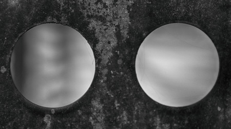 Close up metal wall with two porthole-shaped windows. Monochrome surface and blurred background. Banco de Imagens