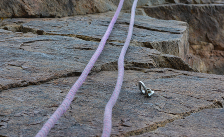 Rope and hook on the rock climbing. Selective focus. Blurred background.