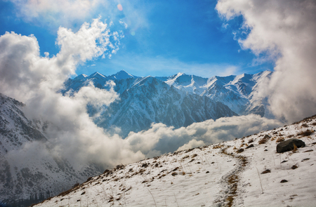 Windows of clouds in mountains. Beautiful misty rock landscape with snow and clouds. Great view of the foggy Ala-Archa National Park in Kyrgyzstan. Banco de Imagens