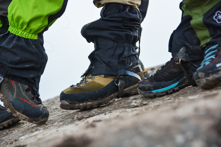 Side View of feet wearing hiking shoes with stone in background. Tourism concept. Selective focus.