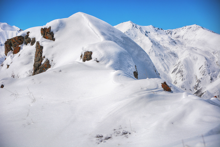 Winter snow covered mountain peaks. Tourists Ala-Archa National Park in Kyrgyzstan.
