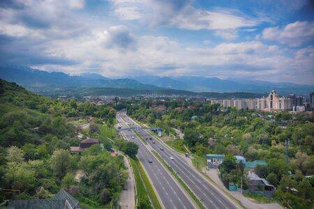 Panoramic view of the city of Almaty, with road, industrial zone, mountains and sky with clouds. Viewed from Kok tobe, Kazakhstan. Banco de Imagens