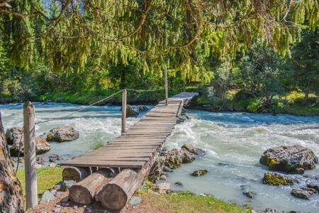 Wood bridge under mountain river. Stock fotó