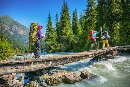 Hikers crossing over wood bridge under mountain river. Stock fotó
