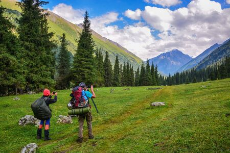 Idyllic summer landscape with hiker Young men with backpack walking along the trail in the mountains and take a photo. Concept of outdoor activities and adventures in nature.