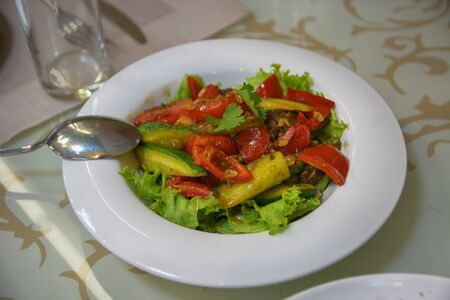 Fresh salad with a tomato, cucumber and greens. Top view of vegetable plate.