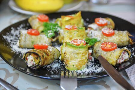 Vegetarian rolls with squash, tomato, cheese and greenery on black plate. Selective focus. Healthy food. Stock fotó