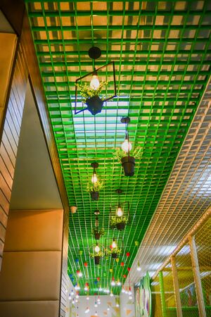 Interior of cafe ceiling with light bulb. Green color. Selective focus.