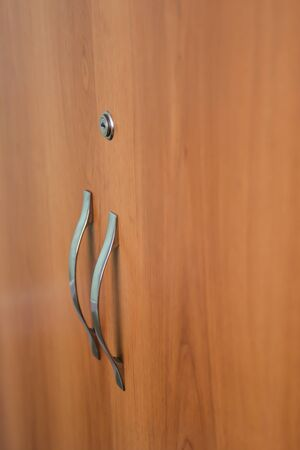 Beautiful doors of cupboard with keyhole and door handle from brass close-up. Background image of wooden doors of locker.