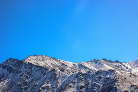 Winter snow covered mountain peaks against blue sky. Kyrgyzstan. Stock fotó
