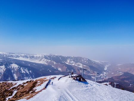 Areal view of winter mountains and blue sky. Landscape. Winter Nature. Flight over ski base. Terskey Alatoo mountains, Tian-Shan, Karakol, Kyrgyzstan. Archivio Fotografico - 142752805