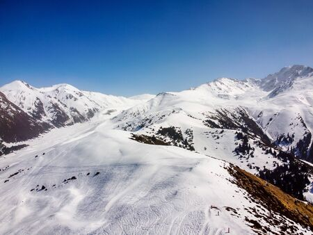 Areal view of winter mountains and blue sky. Landscape. Winter Nature. Flight over ski base. Terskey Alatoo mountains, Tian-Shan, Karakol, Kyrgyzstan. Archivio Fotografico - 142752806