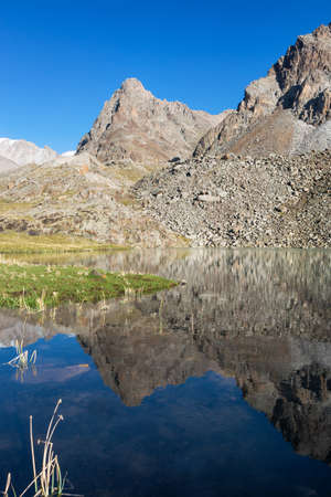 Idyllic summer landscape in the mountains with beautiful fresh green mountain pastures, lake with reflection and clouds. Kyrgyz Alatoo mountains, Tian-Shan, Ala-archa, Kyrgyzstan. Archivio Fotografico - 155469303