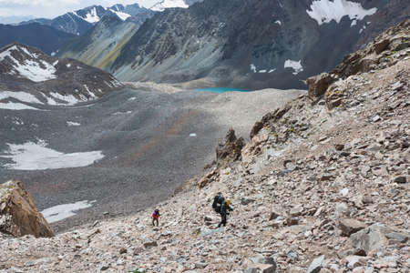 Group of tourists with backpacks lift up mountain trail to glacier in the national park Ala-archa, Kyrgyzstan.