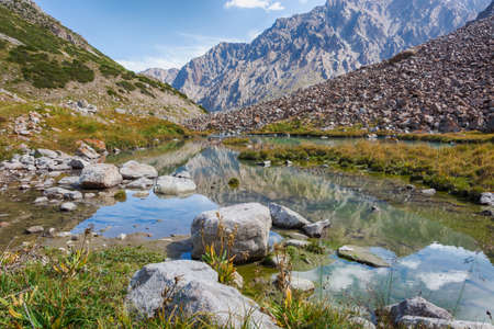 Idyllic summer landscape with hiking trail in the mountains with beautiful fresh green mountain pastures, river with reflection and clouds. Kyrgyz Alatoo mountains, Tian-Shan, Ala-archa, Kyrgyzstan. Archivio Fotografico