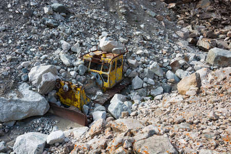 Old destroyed yellow tractor in mountains. Demolition machine. Archivio Fotografico