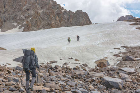 Group of tourists with backpacks lift up mountain trail to glacier in the national park Ala-archa, Kyrgyzstan. Beautiful inspirational landscape, trekking and activity.