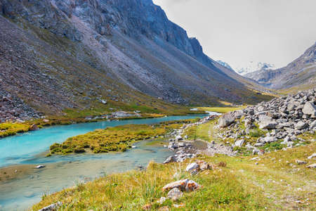 Idyllic summer landscape with hiking trail in the mountains with beautiful fresh green mountain pastures, river. Kyrgyz Alatoo mountains, Tian-Shan, Ala-archa, Kyrgyzstan.