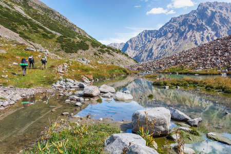 Idyllic summer landscape with hiking trail in the mountains with beautiful fresh green mountain pastures, river with reflection and clouds. Kyrgyz Alatoo mountains, Tian-Shan, Ala-archa, Kyrgyzstan. Archivio Fotografico - 155468629