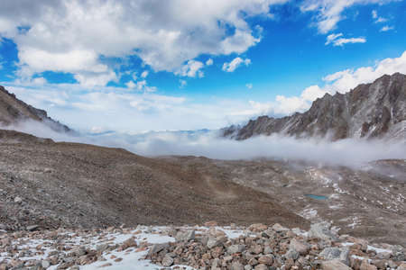 Mountain landscape view in Kyrgyzstan. Rocks, snow and stones in mountain valley view. Mountain panorama.