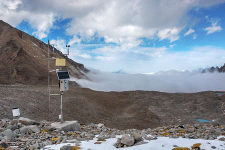 Weather station in mountains. Rocks, snow and stones in mountain valley view. Mountain panorama.